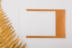 Mockup white greeting card and envelope with golden fern leaves and light background. stock photos