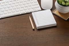 Mockup of white keyboard, mouse, to do list note, pencil and houseplant on wooden table. With copy space royalty free stock image