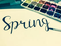 Mockup with a White Page, Word Spring, Paints and Brushes Stock Photos