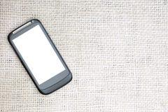 Mockup wizerunek czarny mobilny smartphone z pustym bielu ekranem na rocznika brezentowego stołu białym tle Egzamin próbny up zas Zdjęcie Stock