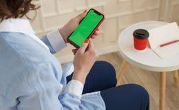 Mockup wizerunek: dziewczyna wewnątrz w błękitnej koszula i spodniach trzyma czarnego telefon komórkowego z chroma klucza ekranem obrazy stock
