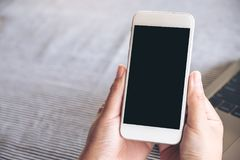 Mockup wizerunek ręki trzyma białego telefon komórkowego z pustym czarnym desktop ekranem, laptopem i zdjęcia royalty free