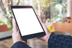 Mockup wizerunek ręki trzyma czarnego pastylka komputer osobistego z pustym desktop bielu ekranem i filiżanką na drewnianym stole Zdjęcie Stock