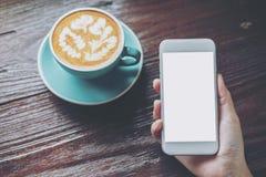 Mockup wizerunek trzyma białego telefon komórkowego z pustym ekranem z błękitną gorącą filiżanką na rocznika drewnianym stole ręk obraz stock