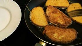 Moczący w jajecznych kawałkach biały chleb lub grzanka, smażący w niecce i obraca z rozwidleniem zdjęcie wideo