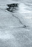 Moczę pękał asfaltowego chodniczek z wodnymi kałużami i raindrops Obrazy Royalty Free