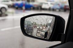 Moczy deszczem samochodowego lustro, rozmyci samochody w lustrze. Obraz Stock