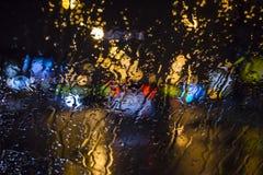 Moczy okno z tłem nocy miasta ruchu drogowego widok Obraz Stock