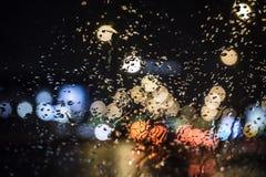 Moczy okno z tłem nocy miasta ruchu drogowego widok Fotografia Stock