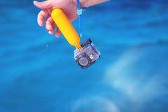 Moczy ręki mienia akcji kamerę w wodoodpornej skrzynce fotografia royalty free
