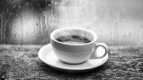Moczy szklanego okno i fili?ank? gor?ca kawa Jesieni chmurny pogodowy lepiej z kofeina napojem Cieszy? si? kaw? na deszczowym dni zdjęcie stock