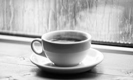 Moczy szklanego okno i fili?ank? gor?ca kawa Jesieni chmurny pogodowy lepiej z kofeina napojem Cieszy? si? kaw? na deszczowym dni obrazy royalty free