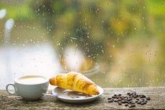 Moczy szklanego okno i fili?ank? gor?cy kofeina nap?j Kawowy nap?j z croissant deserem Cieszy? si? kaw? na deszczowym dniu zdjęcia royalty free