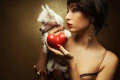 Modèle à la mode tenant le coeur rouge et le petit chien crêté chinois blanc Images stock
