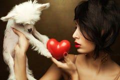 Modèle à la mode tenant le coeur rouge et le petit chien crêté chinois blanc Photographie stock libre de droits