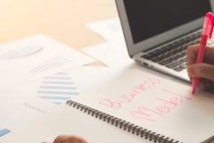 Modèle économique de mot d'écriture de main d'homme d'affaires sur le carnet avec pi photographie stock libre de droits