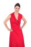 Modèle élégant heureux dans la pose rouge de robe Photographie stock