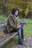 Modèle alternatif reposé sur le banc avec la tablette Images libres de droits