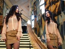 Modèle attrayant de fille avec de beaux regards de cheveux dans un grand miroir Modèle de photo photographie stock libre de droits