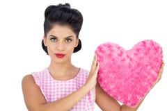 Modèle austère de cheveux noirs tenant un oreiller en forme de coeur rose Image stock