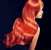 Modèle avec de longs cheveux rouges bouclés Images stock