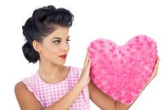Modèle avec du charme de cheveux noirs tenant un oreiller en forme de coeur rose Photo stock