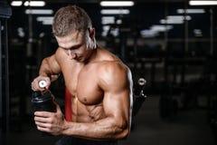 Modèle beau de forme physique tenant un dispositif trembleur dans le muscle de gain de gymnase photos stock