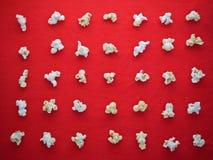Modèle blanc de maïs éclaté sur le tissu rouge Photographie stock
