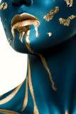 Modèle bleu de beauté avec de l'or liquide sur le visage Photographie stock