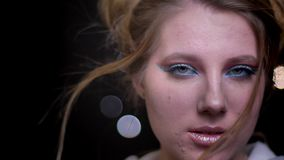 Modèle blond attrayant avec le maquillage lumineux à la mode posant et ajustant ses cheveux sur le fond brouillé de lumières clips vidéos