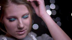 Modèle blond attrayant avec le maquillage lumineux à la mode posant et touchant ses cheveux sur le fond brouillé de lumières banque de vidéos