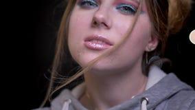 Modèle blond avec le maquillage lumineux à la mode et lentement posant et enrouler souffler ses cheveux sur le fond brouillé de l banque de vidéos