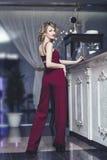 Modèle blond de belle femme dans une salopette rouge un à la mode et photographie stock