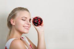 Modèle blond de sourire heureux ayant l'amusement avec des WI d'un petit gâteau de bonbon images libres de droits