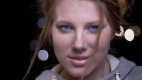 Modèle blond magnifique avec le maquillage lumineux posant à la mode et enrouler souffler ses cheveux sur le fond brouillé de lum banque de vidéos