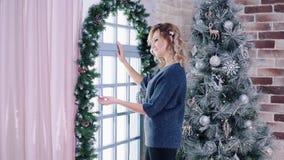 Modèle blond mignon posant près de l'arbre de fenêtre et de Noël clips vidéos