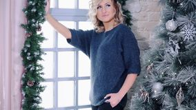 Modèle blond mignon posant près de l'arbre de fenêtre et de Noël banque de vidéos