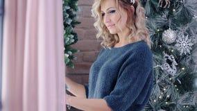 Modèle blond mignon posant près de l'arbre de Noël banque de vidéos