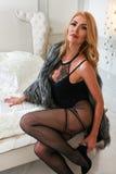 Modèle blond utilisant la lingerie noire sexy, regardant l'appareil-photo avec l'expression de flirt se reposant sur le lit dans  Image libre de droits