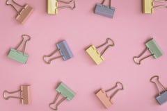 modèle coloré de trombone de configuration plate sur un papier rose Image stock