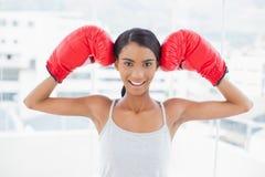Modèle concurrentiel de sourire portant les gants de boxe rouges Photo libre de droits