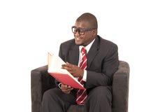 Modèle d'Afro-américain dans le costume gris riant tout en lisant Image libre de droits