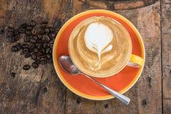 modèle d'art de latte de café, avec des grains de café dans la tasse orange dessus Photo stock