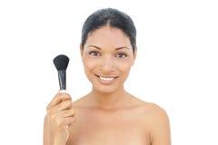 Modèle d'une chevelure assez noir tenant la brosse de fard à joues Photographie stock