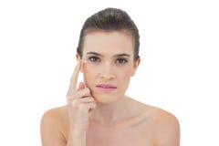 Modèle d'une chevelure brun naturel concentré appliquant la crème de visage Image stock