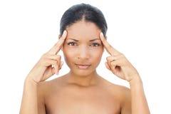 Modèle d'une chevelure noir attrayant ayant un mal de tête Photographie stock