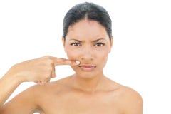 Modèle d'une chevelure noir de froncement de sourcils se dirigeant au-dessus de ses lèvres Photographie stock libre de droits