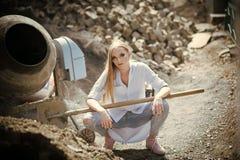 Modèle de beauté avec le maquillage au mélangeur de ciment Travailleuse dans la chemise et des jeans sur le chantier, mode Femme  Image libre de droits