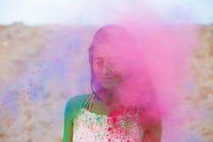 Modèle de brune d'offre posant avec éclater la poudre sèche rose de Holi au désert image libre de droits