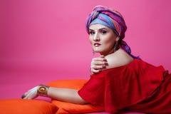 Modèle de brune de fille plus la pose menteuse de taille sur un fond rose dans le vêtement ethnique et le maquillage image stock